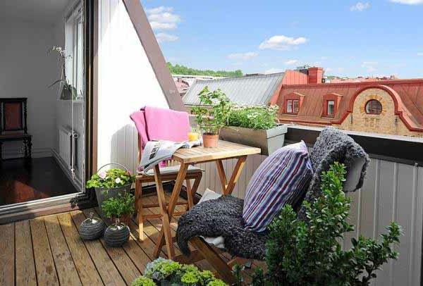holzterrasse mit modernem design - grüne pflanzen und dekokissen