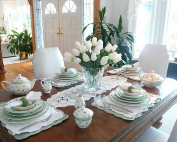 tisch im luxus esszimmer - mit weißen tulpen und porzellangeschirr ausstattten