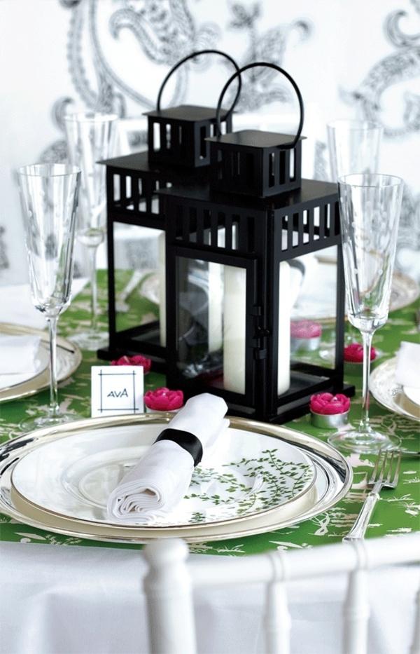 gerollte servietten und große kerzenhälter in schwarz für eine ultramoderne tischdeko