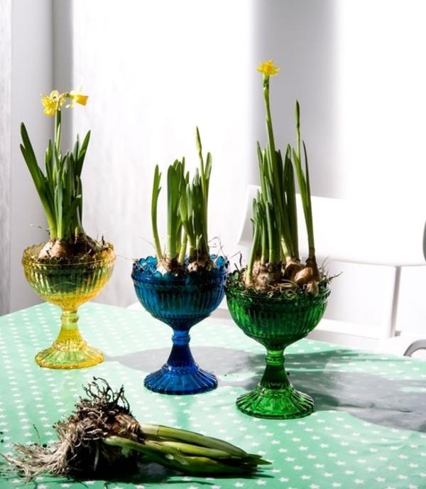 tischdeko mit gläsernen buntfarbigen vasen und wurzeln