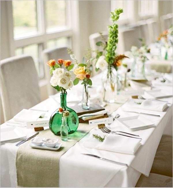 tischdeko mit vasen mit rosen und weißen servietten und decke