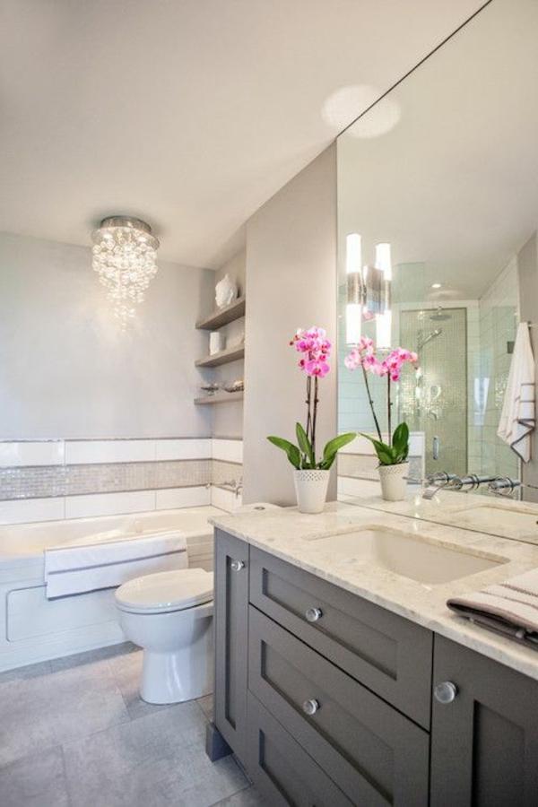 badezimmereinrichtung mit einem kronleuchter aus glas, dekorative blumen und großem spiegel