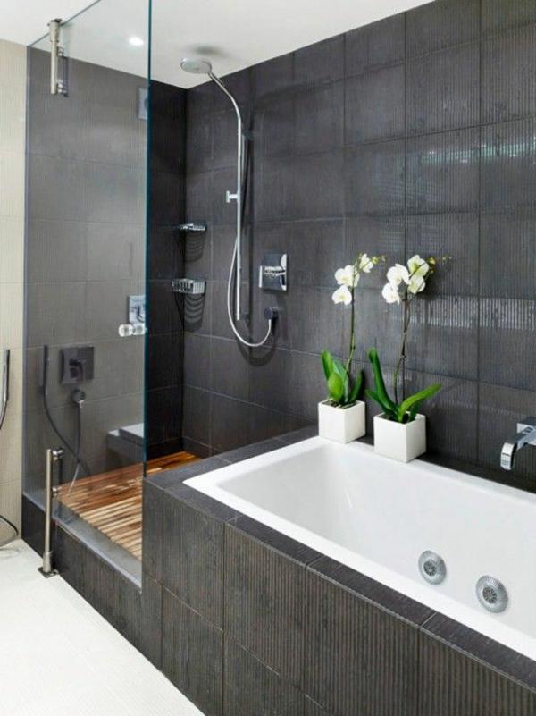 moderne badgestaltung mit einer badewanne, dusche, wand aus glas und zwei blumen