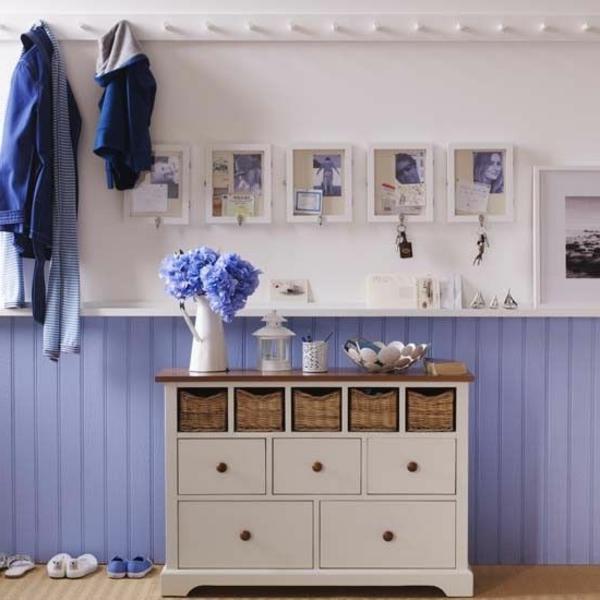 flurgestaltung mit lila und weißen wänden , kleinen bildern an der wand und hänger für kleider