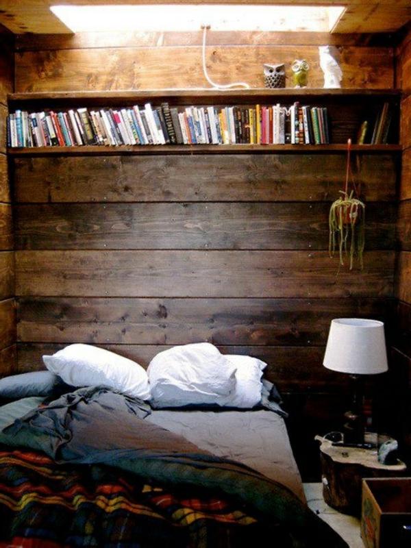 schlafzimmer mit einer holzwand und einem bett mit schönen bettwäschen und kissen