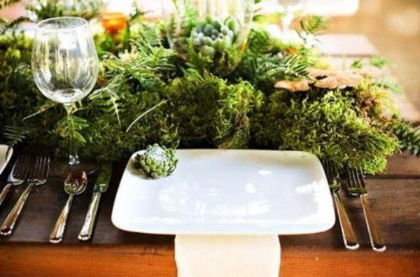 grüne pflanzen und weißer porzellanteller - tisch elegant dekorieren