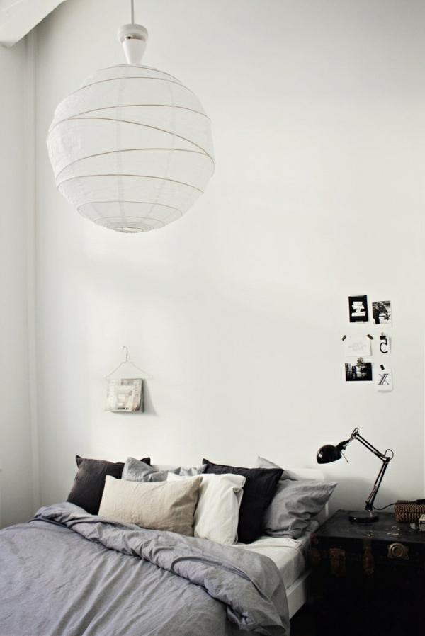weißes schlafzimmer mit einem bett mit bettbezügen in grau