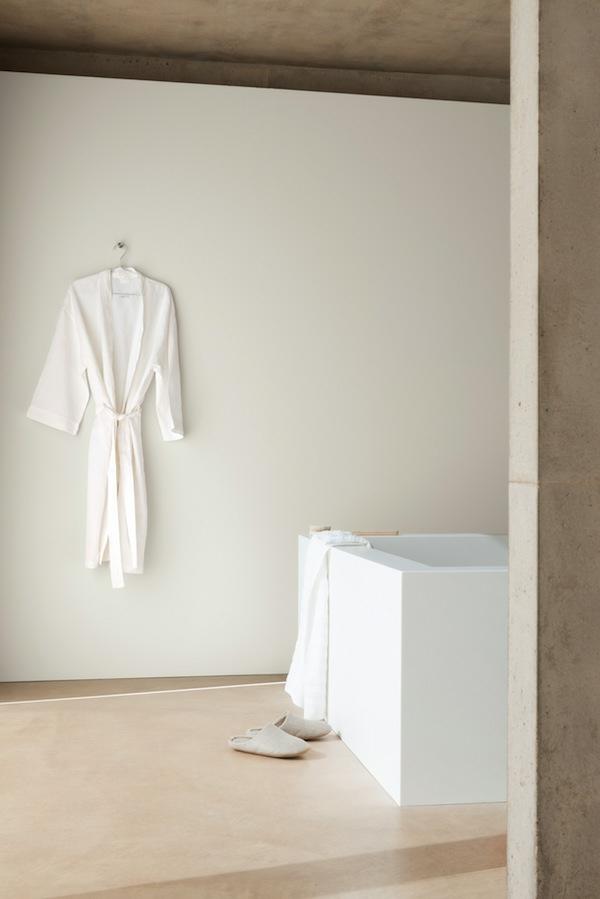 modernes badezimmer mit einer weißen badewanne und einem badeaufzug an der wand