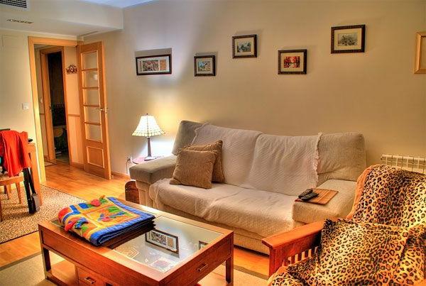 wohnzimmer gestaltung mit einem nesttisch aus holz, einem leopard sessel, bildern an der wand