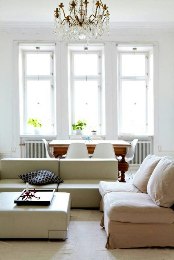 Helles Wohnzimmer mit beige Sofas und Ottomane statt Tisch