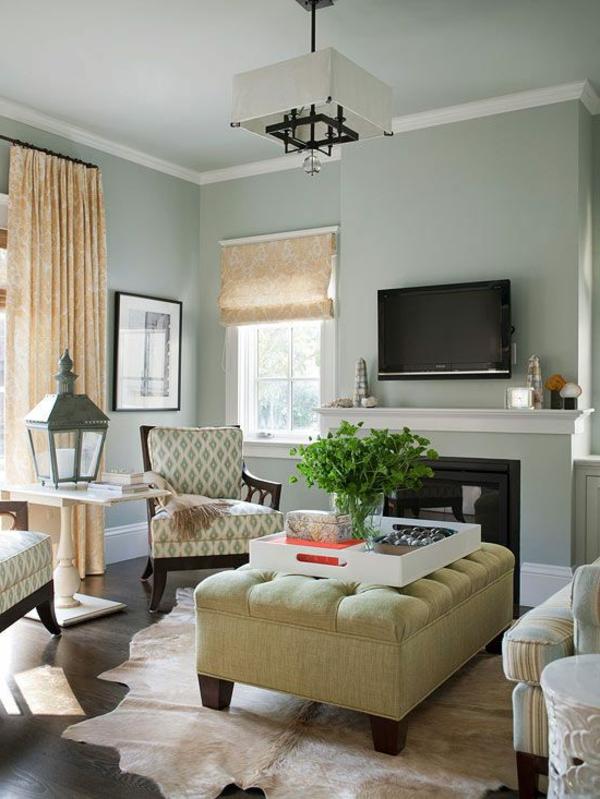 Ein Wohnzimmer im hellblau, die besonders frisch aussieht mit einen gelben Ottomane
