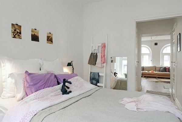 Schlafzimmer-gestalten-im-skandinavischen-Stil-Holztreppe-als-Kleiderbügel-persünliche-Photos-als-Wand-Deko