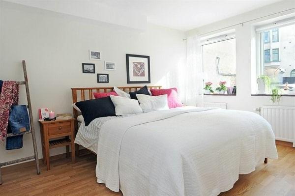 Schlafzimmer-gestalten-im-skandinavischen-Stil-größes-Bett-mit-vielen-Kisten-weiße-Wände-Holztreppe-für-die-Kleidung
