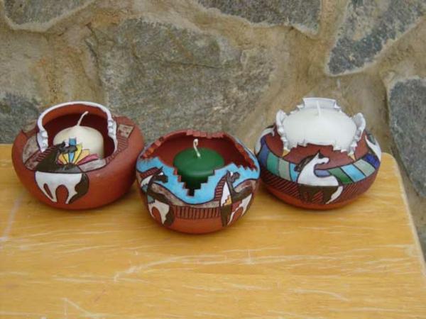 interessante kerzenhalter und drei dekorative kleinen kerzen in weiß und grün