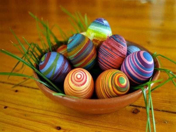ostern deko mit einem teller mit gras und bunt bemalten eiern