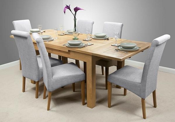 eleganter-ausziehbarer-esstisch-mit-vielen-grauen-stühlen und einer dekorativen blume