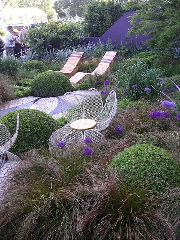 hölzerne-liegestühle-im-mediterannen-garten mit grünen pflanzen