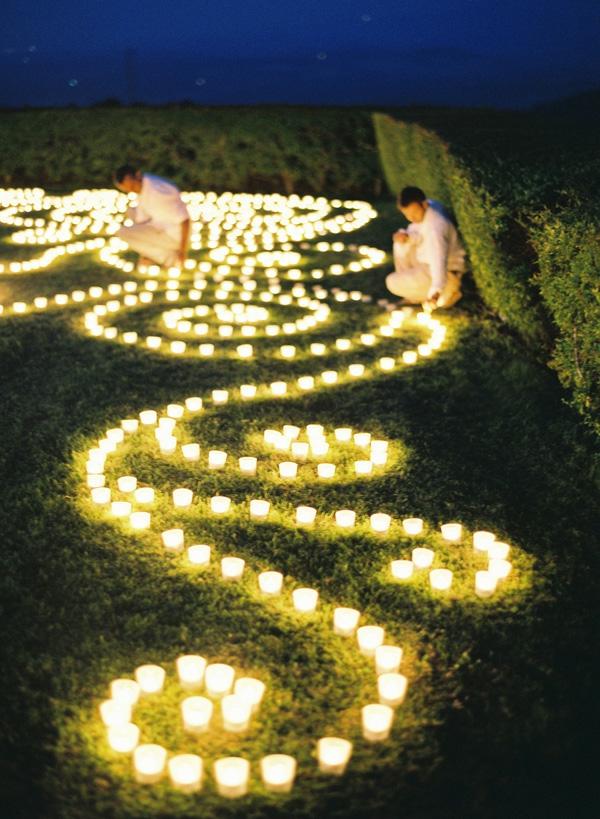 viele kleine Kerzen auf dem gras als schöne kerzen dekoration zur hochzeit