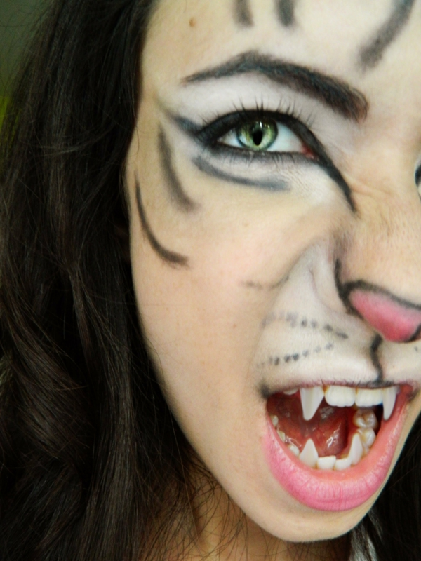katze-schminken-halloween-mädchen- mit zähnen einer vampirin