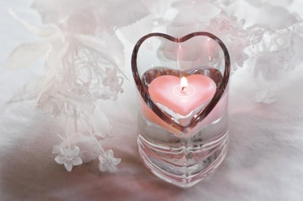 kerzenhalter aus glas und eine kleine rosige kerze in herzenform