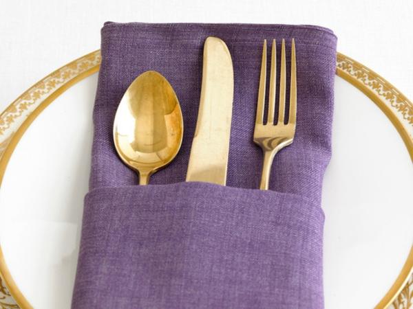 goldenfarbiges geschirr und lila haupr farbe für servietten