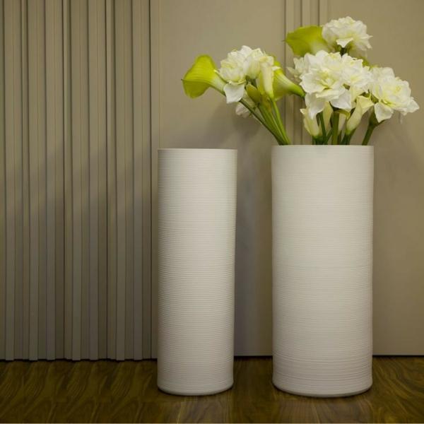 moderne-bodenvasen-in-weiß-mit-blumen- hintergrung in ockra