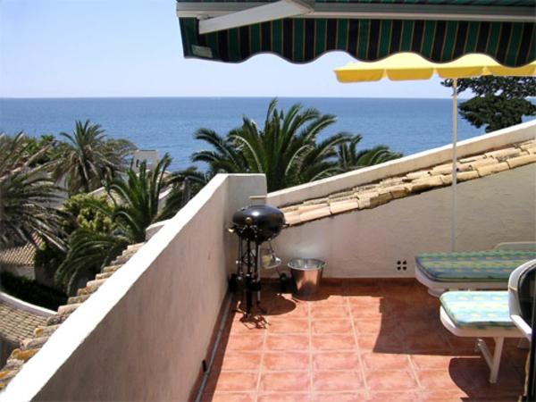 moderne-terrassengestaltung-sichtschutz- zwei liegestühle und zwei sonnenschirme