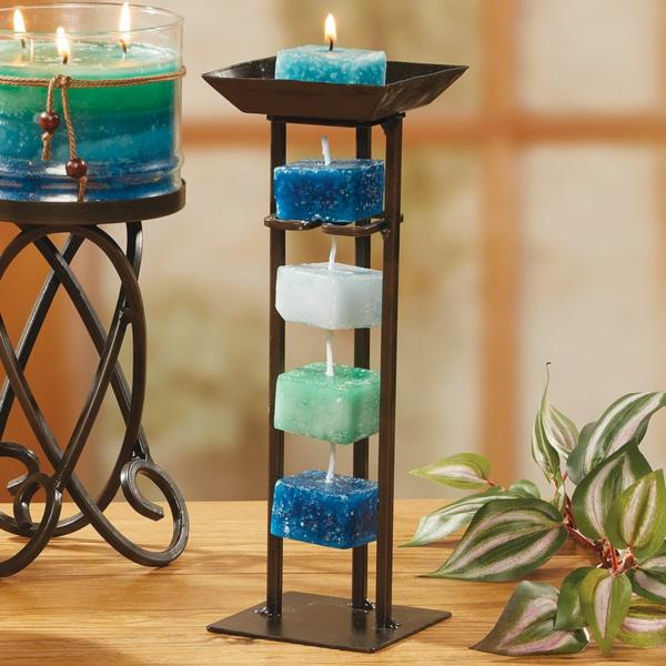 kleine kerzen in weiß blau und türkis mit interessanten kerzenhaltern