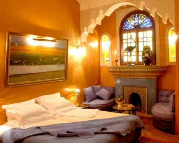 luxus kamin und orange farbschemen im eleganten orientalischen schlafzimmer