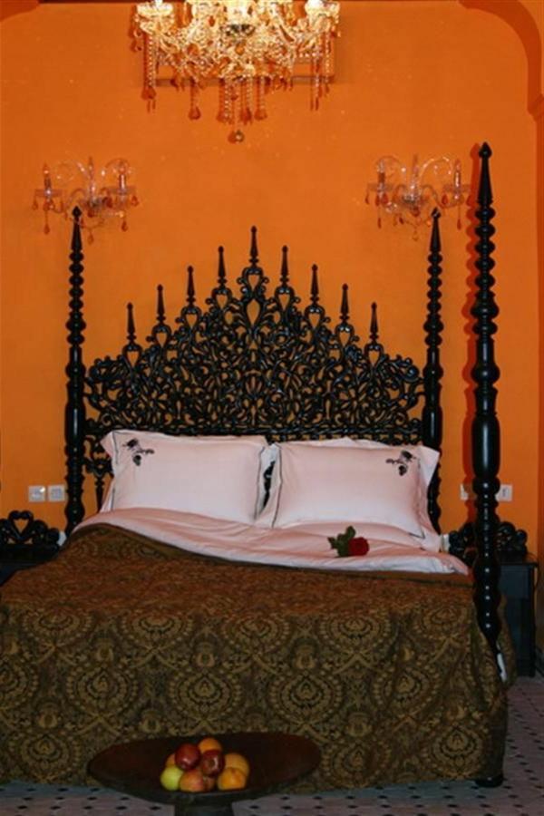 aristokratsich aussehendes kopfbrett im luxus orientalischen schlafzimmer mit oranger wandgestaltung