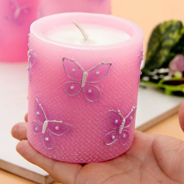 schmetterlinge figuren als dekoration für eine rosige kerze