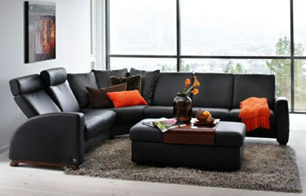 schwarzes-sofa-mit-orangen-kissen
