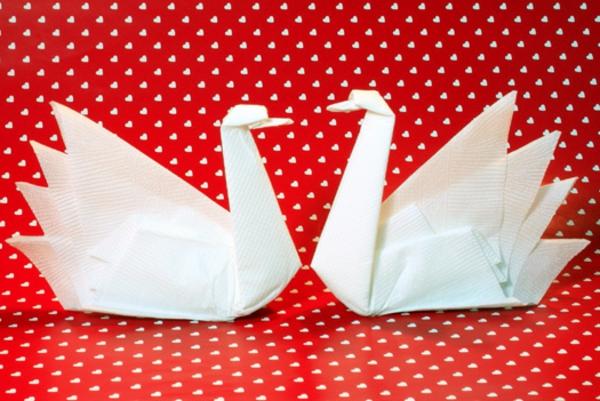 servietten-falten-schwäne- roter hindgrund