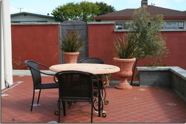 terrasse-mediterran-gestalten- mit einem zaun und topfpflanzen