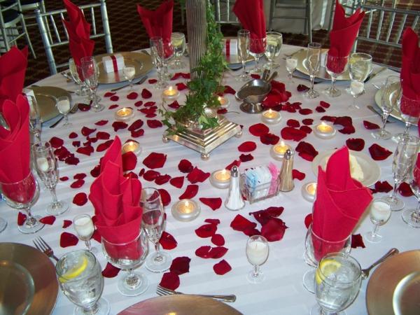 rote servietten in gläsern weiße decke und rote rosenblätter - ideen für partydeko