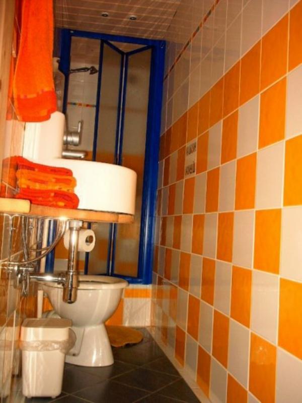 toilette-orange-und-weiße-fliesen- klein und gemütlich