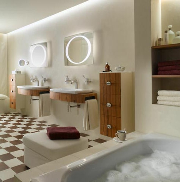 zwei runde spigel mit leuchten an der wand im luxus badezimmer mit einer badewanne