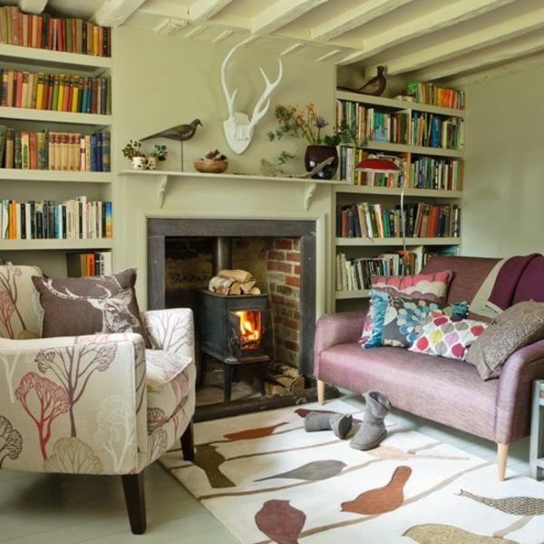 wohnzimmer-mit-bücherregalen-im-landhausstil- kaminofen und sofas mit bunten dekokissen