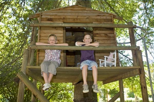 zwei-kinder-baumhaus-sitzen auf dem balkon