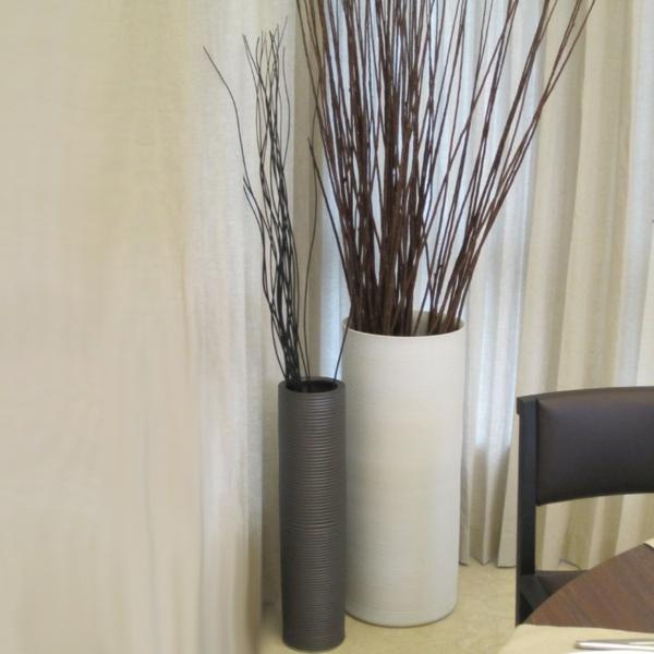 zwei-moderne-bodenvasen-aus-keramik - neben durchsichtigen gardinen