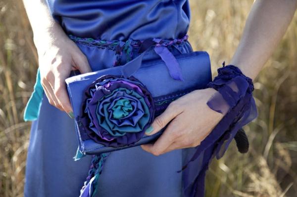 clutch nähen  - eine frau mit einer schönen blauen handtasche - filzblume