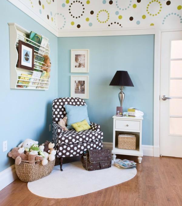 babyzimmer-tapeten-blau- plüschtiere und ein sessel mit dekokissen darauf