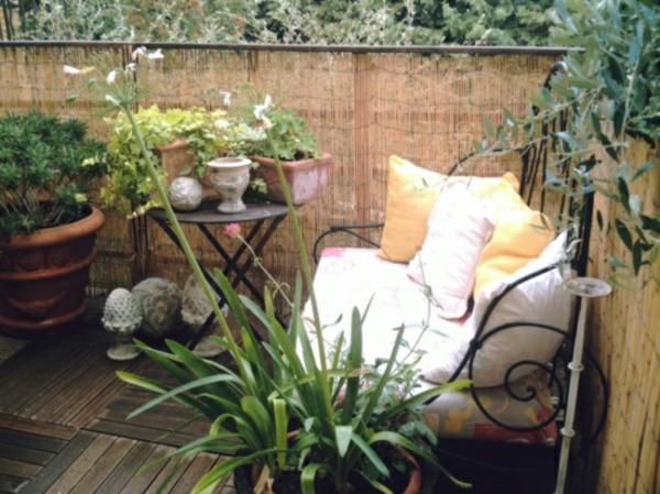 balkon-sichschutz-bambus-grüne-pflanzen-dekorative-kissen-auf-dem-sofa