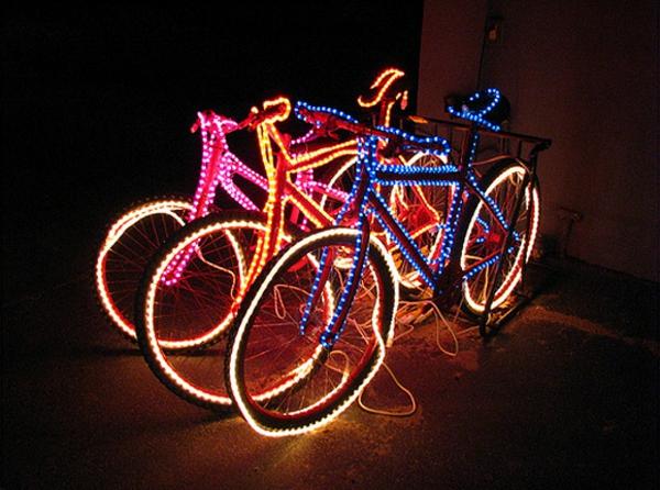 drei-fahrräder-mit-led-beleuchtung-deko-idee im zimmer, das dunkel ist