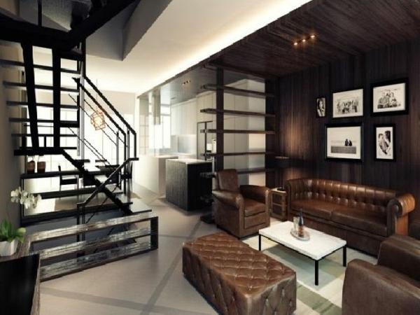 elegantes-wohnzimmer-braune-farbtöne- treppen und ledersofa mit zwei sesseln und einem hocker