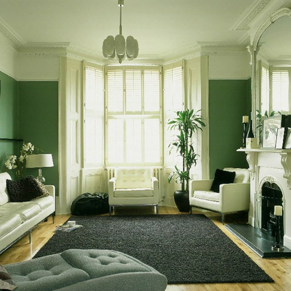 farbgestaltung-wände-grüne-farbtöne - sofa mit dekokissen und ein kamin