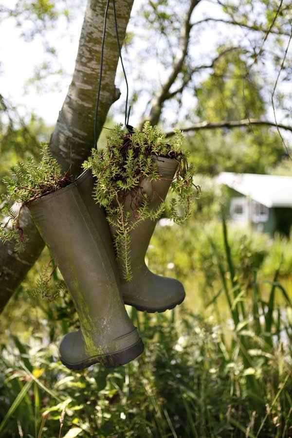 gartendekoration aus hängenden stifeln mit pflanzen machen - vom baum hängen