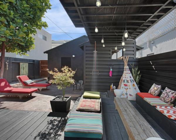 holzboden-balkon-moderne-möbelstücke - liegestühle in rot und sofa