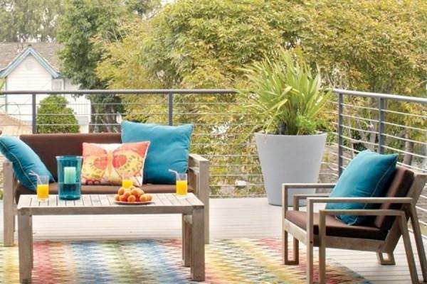 holzfliesen-terrasse-bunter-teppich - dekokissen und sofa