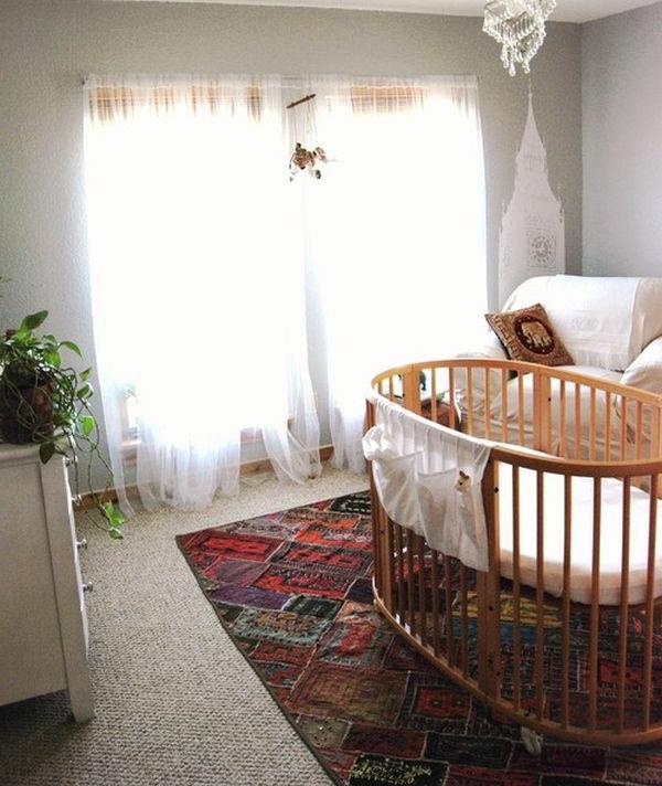 kinderbettchen-rund-teppich-im-babyzimmer - kronleuchter und grüne pflanze